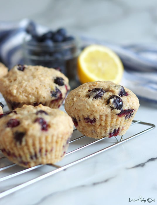 Corner of a wire cooling rack with 3 visible lemon and blueberry muffins on top. Blurred half lemon and glass jar of blueberries in the background along with a crumpled white and blue striped towel.