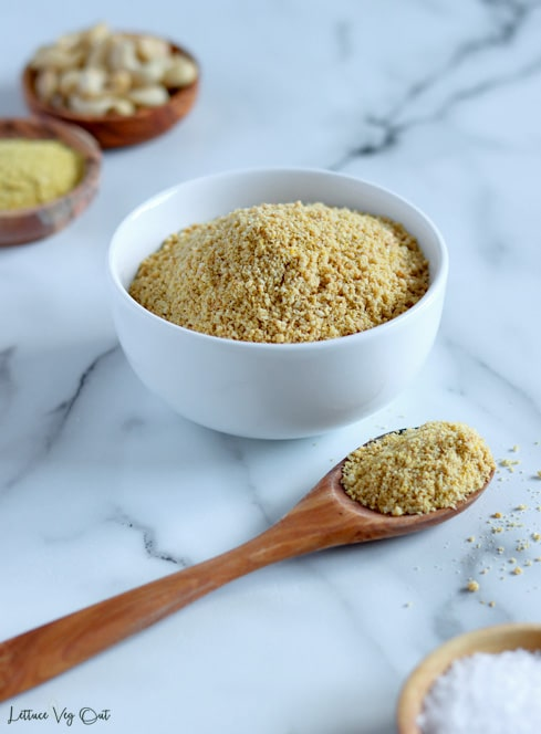 Bowl filled with crumbly vegan parmesan cheese (golden brownish-yellow color from the ground cashews) sits behind a wooden spoon filled with the crumbly cheese substitute. Bottom right corner shows a small wood dish filled with salt and back left corner shows two small wood dishes filled with cashews and nutritional yeast.