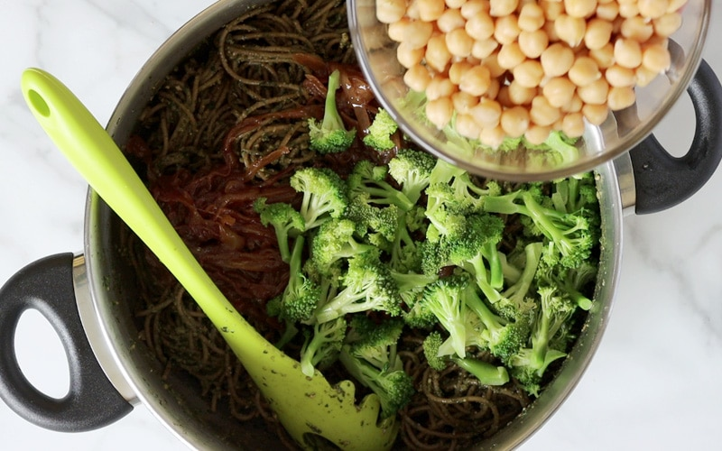 Top view of a large pot filled with pesto pasta, a large green pasta spoon and cooked broccoli florets. A glass bowl full of chickpeas is being held over the pot, in the top right corner.