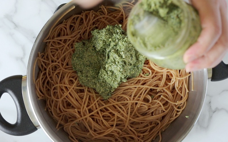 Top view of a large pot filled with cooked spaghetti pasta with a large pile of pesto sauce in the center. In the top right corner of the image there's a blurred hand holding a jar of pesto with a spoon in the pesto, scooping it out.