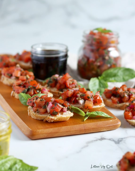 Straight on image of a long wood board topped with tomato bruschetta pieces made on sliced baguette and garnished with basil; only the front few pieces are in focus. Around the board are other bruschetta pieces, and jars filled with bruschetta mix, balsamic vinegar and olive oil.