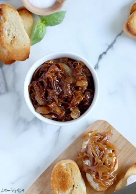Top view of a small white bowl filled with dark brown caramelized onions. Bowl sits on white-grey marble with toasted crostini, basil and a wood dish of salt in the top left corner and the corner of a wood board with crostini pieces that are topped with caramelized onions in the bottom right corner.