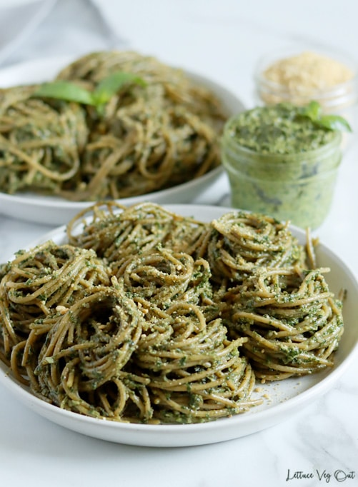 White plate topped with many piles of swirled spaghetti noodles that are coated with green pesto sauce. A second plate of pesto pasta sits blurred in the back. A jar of pesto and jar of parmesan cheese sit between the plates, to the right.