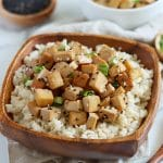 Square cropped image of a square wood bowl filled with rice that is topped with golden brown baked tofu cubes and garnished with black sesame seeds and chopped green onion. Bowl sits on light brown towel.