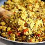 Close up of a large wood spoon of tofu scramble that is bright yellow in color, cooked with mushrooms and red peppers. The spoon rests on a pan-full of tofu scramble.