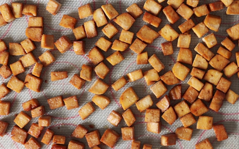 Top view of a baking tray that is covered with dark golden brown cubes of baked tofu.