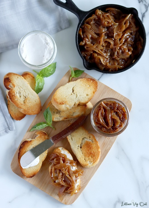 Top view of a wood board topped with toasted crostini, one of which has a knife resting on it and another topped with caramelized onions. A small glass jar of caramelized onions and sprigs of basil are also on the board. Additional crostini sits to the left of the board and a small cast iron pan of onions is in the top right corner.