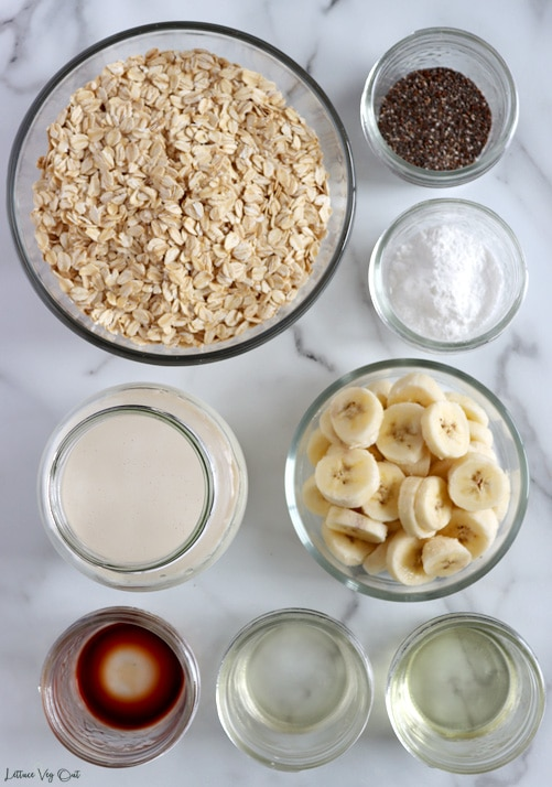 Top view of an arrangement of ingredients in glass jars and bowls. From top left moving right then down: rolled oats, chia seeds, baking powder, plant-based milk, sliced banana, vanilla extract, vinegar, oil.