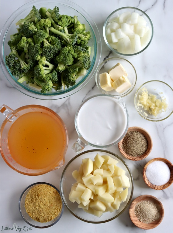 Top view of an arrangement of ingredients in glass jars, bowls and wood dishes. From top left moving right then down: broccoli florets, chopped onion, vegan butter, minced garlic, vegetable broth, coconut milk, black pepper, nutritional yeast, diced potatoes, salt, Herbamare seasoning.