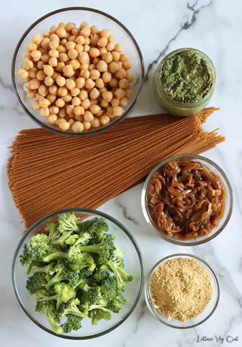 Arrangement of ingredients in glass bowls/ jars for making pesto pasta. From top left moving right then down: cooked chickpeas, prepared pesto sauce, raw spaghetti noodles, caramelized onions, raw broccoli florets, vegan parmesan cheese.