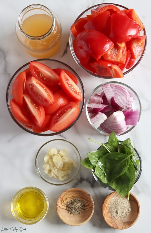 Top view of an arrangement of ingredients in glass or wood dishes. From top left moving right then down: vegetable broth, chopped red pepper, chopped tomato, chopped red onion, sliced garlic, basil leaves, olive oil, ground black pepper, seasoning salt.