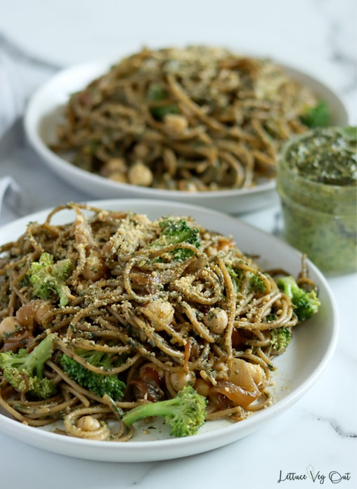 Close up of a plate of pesto pasta (spaghetti) loaded with broccoli, chickpeas and caramelized onions with a sprinkle of parmesan cheese on top. A second plate of pasta is blurred in the back and a small jar of pesto sauce sits between the plates to the right.