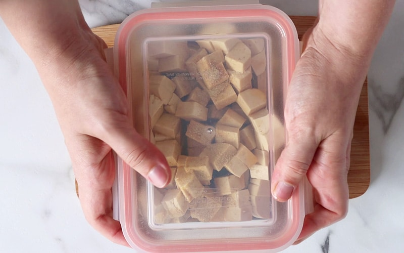 Top view of two hands placing a plastic lid on a rectangular container. Inside the container are cubes of tofu.