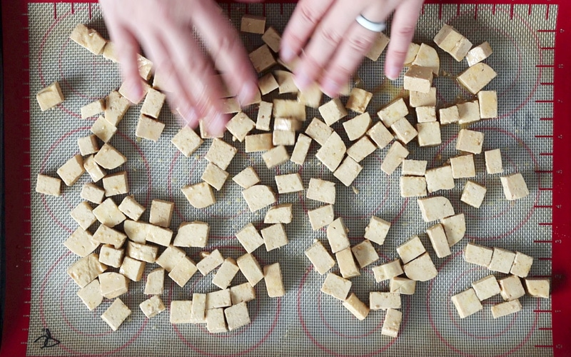 Top view of a baking tray that is covered with a silicone mat and cubes of marinated tofu that are a pale brown color. Two hands are spreading the tofu cubes around the tray.