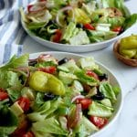 Square cropped image of Two round white plates topped with tossed Italian salad (leaf lettuce, tomato, red onion, cucumber, black olives, artichoke, croutons) with white-grey marble background. White blue striped towel along left edge
