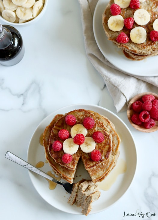 Top view of a plate with a stack of pancakes, with a bite cut out of the stack resting on a fork towards the bottom of the plate. The pancake stack is topped with raspberries and banana and a second stack of pancakes sits partially cropped out in the top right corner of the image. Image is decorated around the edges with a bowl of banana slices and jar of maple syrup in the top left and a dish of raspberries on the right edge.