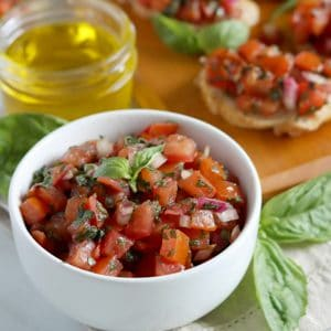 Square cropped image of a small white bowl filled with prepared tomato bruschetta mix sitting in front of a long wood board topped with bruschetta pieces made on baguette with lots of basil leaves for garnish.