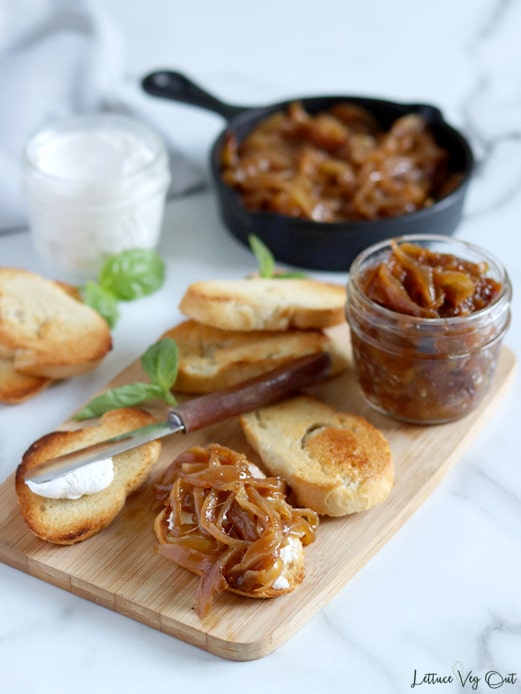 Toasted crostini arranged on a light wood board with one crostini topped with caramelized onions and another with a knife resting on it. A small glass jar of caramelized onions sits in the back right corner of the board. Extra crostini, a jar of cream cheese and a cast iron pan filled with caramelized onions are slightly blurred in the background,