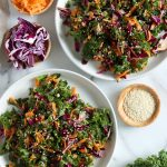 Square cropped image of the top view of two large white plates each loaded with a chopped kale, red cabbage and carrot slaw salad, with white sesame seeds sprinkled on top. Two small wood dishes, one with grated carrot and the other with sliced red cabbage, sit in top left corner while a third wood dish of white sesame seeds sits to the center-right of image.
