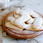 Square cropped image of Pile of ladyfinger cookies, topped with sprinkled icing sugar, on a round wood board with white-grey marble background.