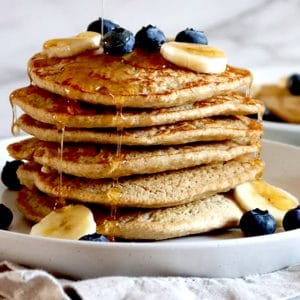 Square cropped image of a plate of vegan oat flour pancakes with blueberries, bananas and maple syrup