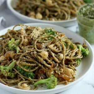 Square cropped image of a close up of a plate of pesto pasta (spaghetti) loaded with broccoli, chickpeas and caramelized onions with a sprinkle of parmesan cheese on top. A second plate of pasta is blurred in the back and a small jar of pesto sauce sits between the plates to the right.