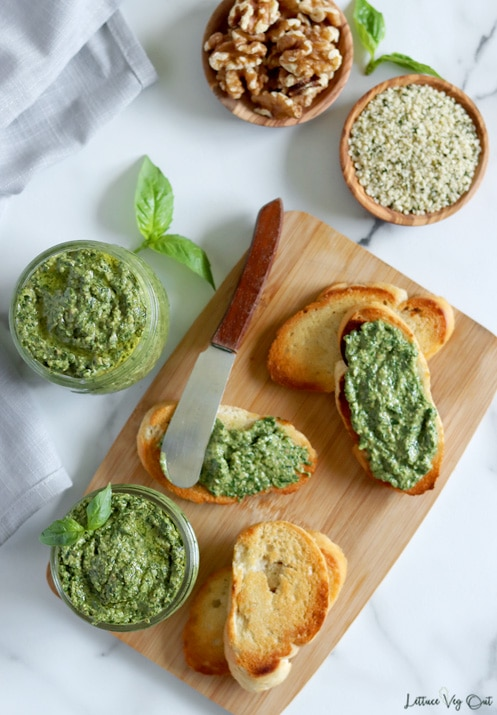 Top view of a small rectangular board topped with toasted crostini, some of which are topped with green pesto sauce, along with a small jar of pesto in the bottom left corner. A second jar of pesto sits to the left of the board. Two small wood dishes, with walnuts and hemp seeds, sit in the top right of the image.
