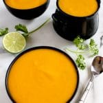Square cropped image of three small black bowls of creamy pumpkin coconut soup sitting on white-grey marble that is decorated with cilantro sprigs and lime.