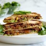 Square cropped image of Stack of three quesadilla triangles stacked on a white plate, garnished with fresh jalapeno slices and cilantro. Two small glass bowls of cilantro, lime wedges and jalapeno slices blurred in back left. White-grey marble background.