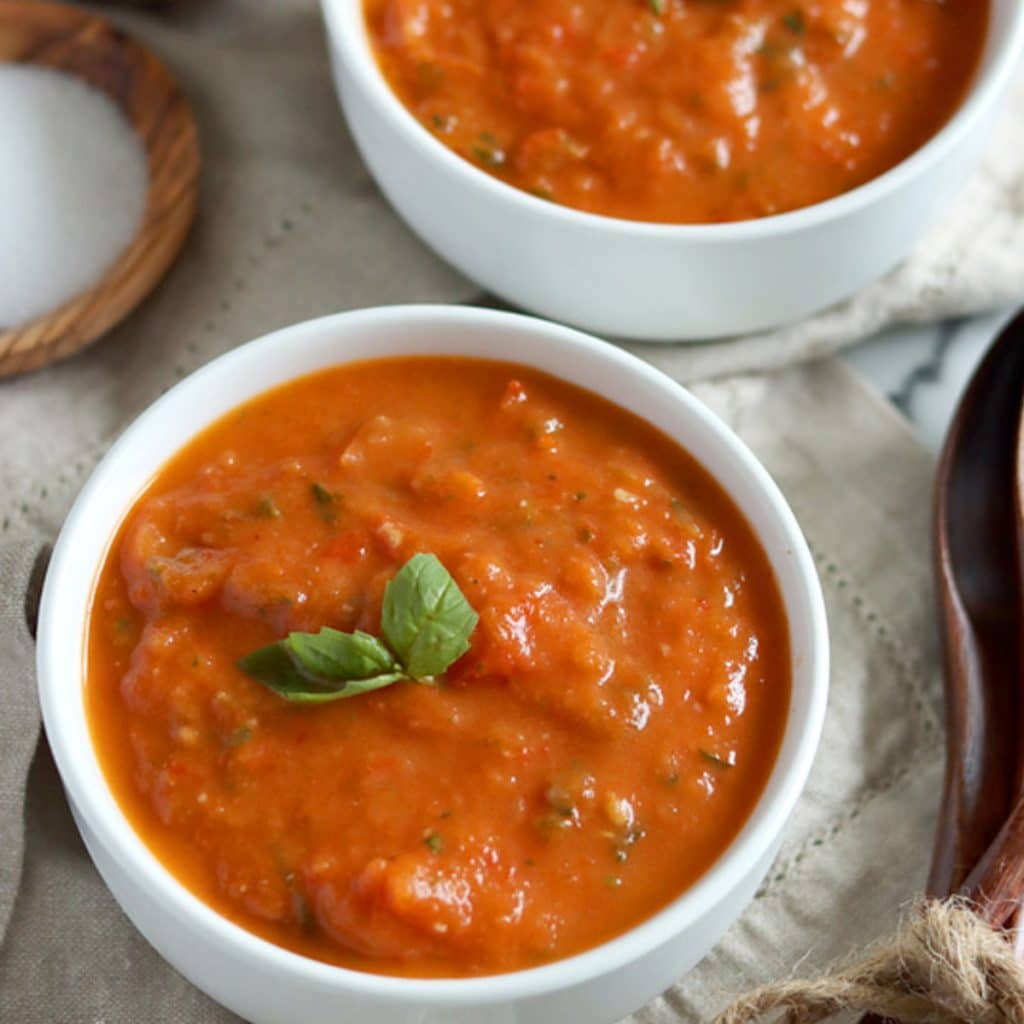 Square cropped image of a close up of two small white bowls filled with chunky roasted red pepper and tomato soup, garnished with a basil leaf. Bowls sit on a light brown towel with wood spoons to the right and wood dishes of salt and pepper to the back left.