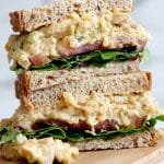 Square cropped image of a sandwich cut in half and stacked up on wood board; sandwich made with brown bread, lettuce, tomato and loaded with creamy mashed chickpeas.