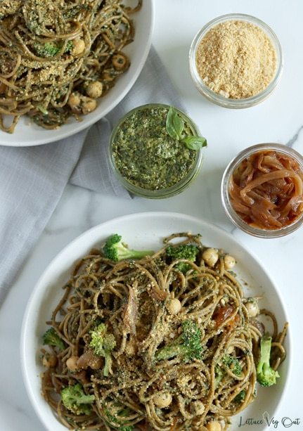 Top view of a plate of pesto spaghetti pasta with a quarter of a second plate of pasta in the top left corner. Above the main plate, in the top right are 3 small jars filled with parmesan cheese, pesto sauce and caramelized onions.