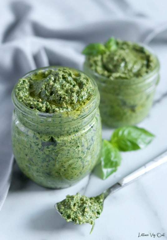 Two jars of pesto sauce, topped with a drizzle of olive oil sit on white-grey marble with a blurred grey towel crumpled behind them. The front jar is slightly larger than the back one. A spoonful of pesto rests in front of the jars.