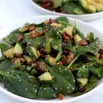 Square cropped image of a white plate full of tossed spinach salad with cucumber, hemp seed and nuts.