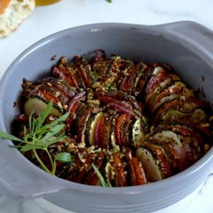 Square cropped image of a round ceramic baking dish filled with thinly sliced, roasted vegetables (tomato, zucchini, eggplant and onion)