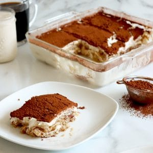 Square cropped of White plate with square of vegan tiramisu (layers of vanilla ladyfingers, cream and cocoa powder on top). A second plate with tiramisu slice in bottom right corner with a small metal sifter of cocoa powder to the center right of image. Square glass dish of sliced tiramisu in back with coffee and milk in glass mugs.