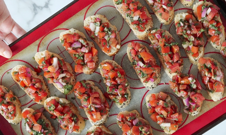 Top view of a baking tray lined with a silicone mat and topped with 3 neat rows of baguette slices each topped with tomato-basil bruschetta mix.