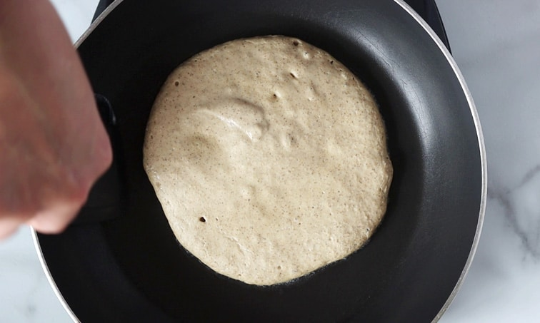 Large pancake in a black pan with a couple bubbles in the top. A hand holding a black spatula is preparing to flip the pancake.