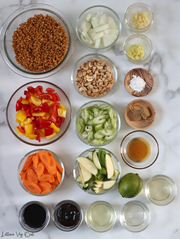 Top view of an arrangement of ingredients in glass bowls, jars and small wood dishes. From top left working right then down: cooked brown lentils, chopped onion, minced garlic, grated ginger, cashew pieces, corn starch, red and yellow bell pepper, sliced celery, brown sugar, sesame oil, sliced carrot, sliced zucchini, a lime, mirin, soy sauce, hoisin sauce, vinegar, oil.