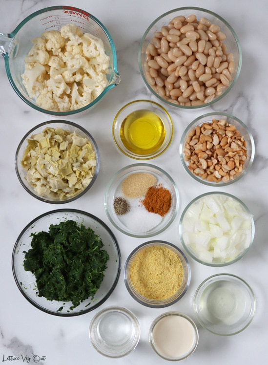 Top view of an arrangement of ingredients in glass bowls and jars. From top left working right then down: cauliflower florets; cooked white beans; olive oil; chopped artichoke; cashew pieces; spices (garlic powder, Old Bay, black pepper, salt); cooked chopped spinach; nutritional yeast; chopped onion; water; plant-based milk; liquid from the canned artichoke.