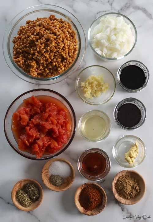 Top view of an arrangement of ingredients in glass or wood bowl. From top left working right then down: cooked brown lentils; chopped white onion; minced garlic; soy sauce; canned diced tomatoes; apple cider vinegar; molasses; Dijon mustard; maple syrup; oregano + basil; salt + pepper; chili powder; ground cumin.