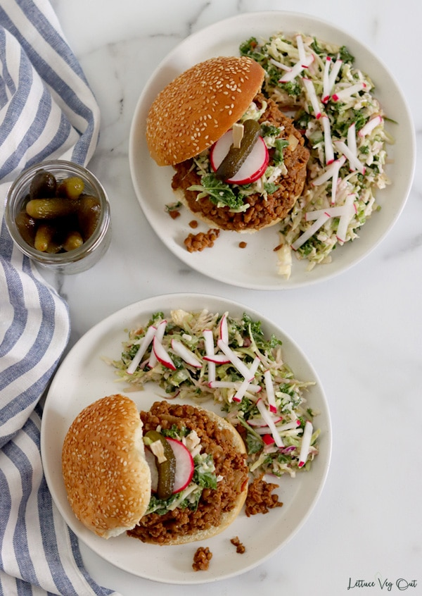 Top view of two white plates sitting on grey marble. Each plate has a bun topped with lentil sloppy joe mixture, some slaw and a garnish of radish slices and a small pickle on a large toothpick with the top bun resting to the side of the sandwich. Slaw with kale and radishes covers half of each plate.