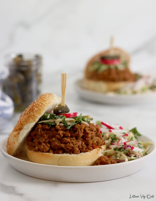 Straight on view of a white plate with a bun loaded with lentil sloppy joe mixture and topped with a bit of slaw and a garnish on a toothpick (radish slice and pickle). The top bun rests to the left of the sandwich and more slaw with radishes covers the right half of the plate. A jar of pickles and second plate with a sloppy joe sandwich on it sit blurred in the background.