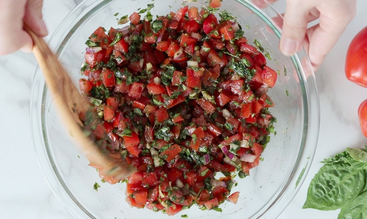 Top view of a large glass bowl filled with tomato basil bruschetta mix. One hand is stirring the mix with a large wooden spoon and the other hand holds the edge of the bowl.