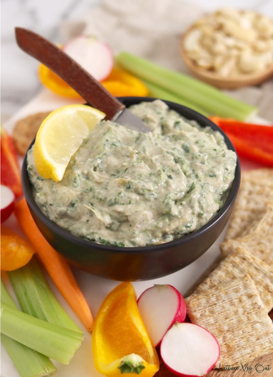 Small black bowl filled with spinach artichoke dip with a wooden knife in it, garnished with a lemon wedge. Bowl sits on a board loaded with square wheat crackers and cut vegetables (radish, peppers, celery and carrots).