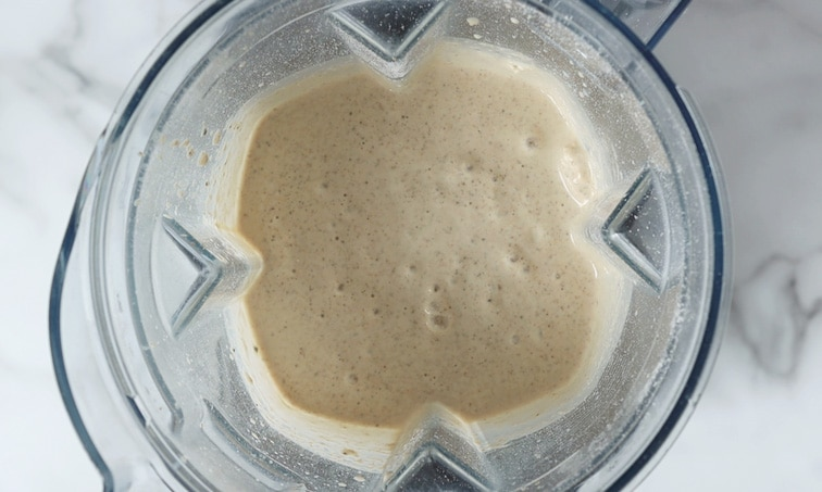 Top view of a blender filled with blended pancake batter that has a few bubbles in it.