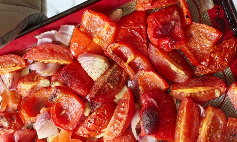 Close up of roasted tomatoes, red peppers, onion and garlic on a baking tray showing the slightly browned topes of the pepper skin.