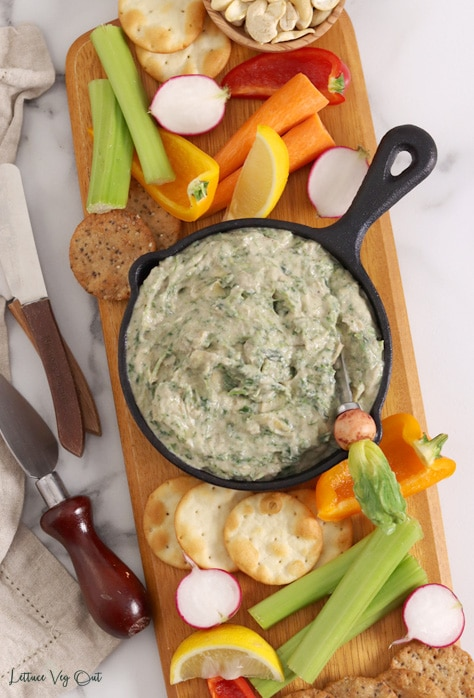Top view of a small cast iron pan filled with spinach artichoke dip with a knife in it that has a radish-shaped handle. Pan sits on a long wood board topped with crackers and vegetables, with butter and cheese knives to the left.