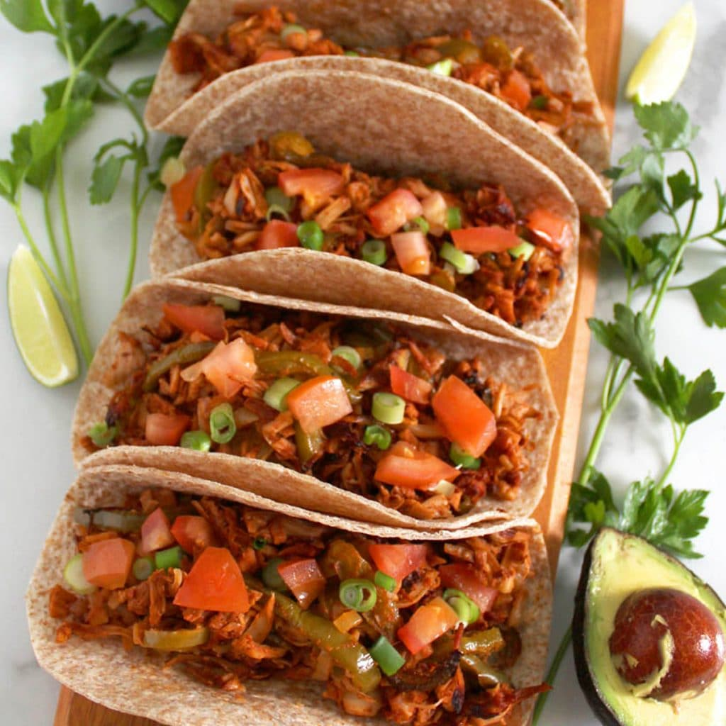 Square cropped image of Row of 5 jackfruit fajitas on wooden board surrounded by lime, avocado and cilantro