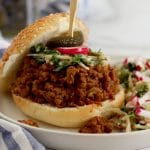 Square cropped image of a close up of a sloppy joe sandwich on a sesame seed bun with the top bun resting to the back left of the sandwich. The sandwich is garnished with a radish and pickle on a toothpick.